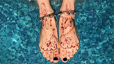Sexy painted henna feet swim in the pool