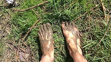Hot sexy teen walking near the river, put feet in the mud
