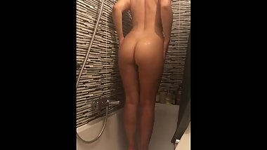 Petite young girl teases herself in the shower