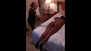 Catherine gets spanked by Angela laying flat on the bed